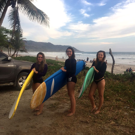 Three female surfers with boards on the beach.